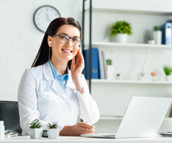 cheerful doctor in earphones having online consultation with patient on laptop in clinic office